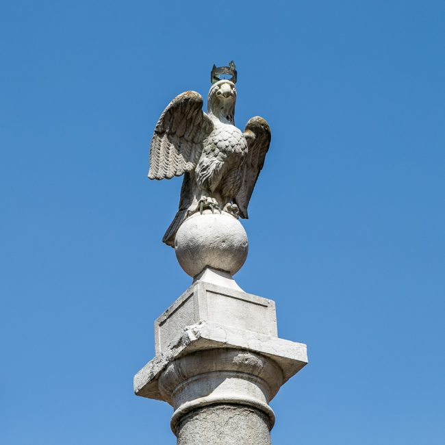 The eagle on top of the column in the center of the square (also called Eagle Square) where stands the palace