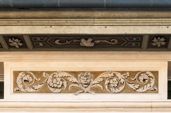Particolare delle decorazioni sotto la gronda con rose e simboli dei Rasponi (teste di moro e zampe di leone)
