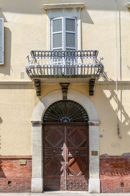 Il portale ad arco ed il balcone sovrastante, con ringhiera barocca