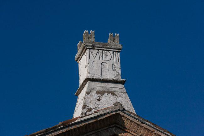 Emblema dei Monaci di Porto scolpito su di un comignolo dell'edificio, visibile dai giardini pubblici.