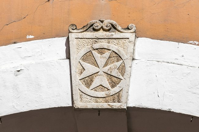 Il portale sinistro con la croce dell'Ordine di Santo Stefano nella chiave di volta