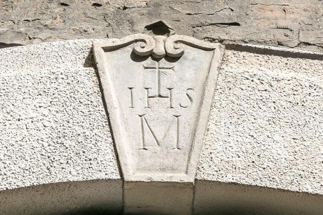 Il portale destro con il monogramma di Cristo nella chiave di volta