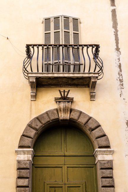 Balconcino con mensole in marmo e ringhiera barocca sopra al portale d'ingresso